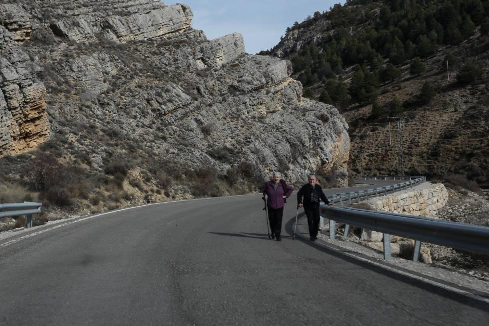 Dos mujeres pasean por la carretera comarcal, en la zona de los Montes Universales.