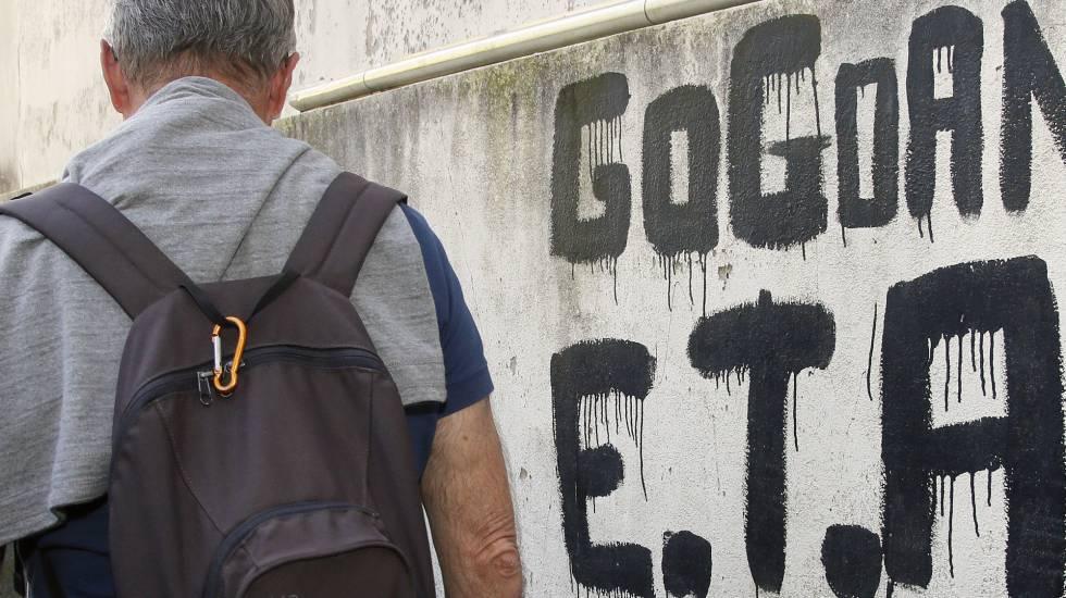 "Un hombre camina junto a una pintada que reza ""ETA, País Vasco y Libertad""."