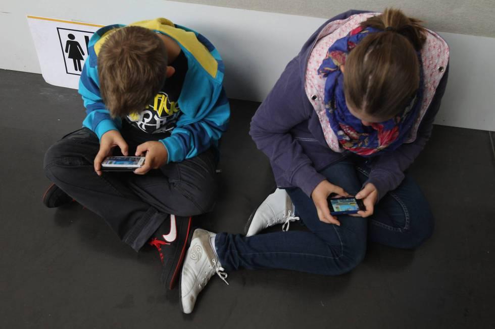Dos niños ensimismados con sus móviles.