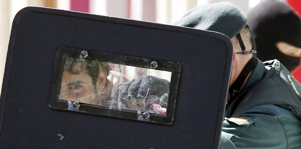 Varios guardias civiles trasladan a Eneko Compains tras registrar su domicilio de Pamplona.