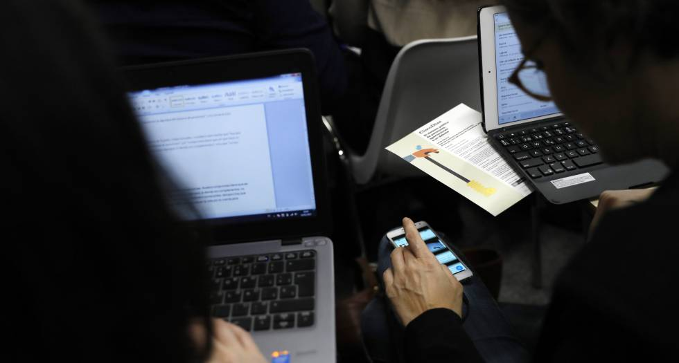 Dos personas trabajan con ordenadores portátiles.