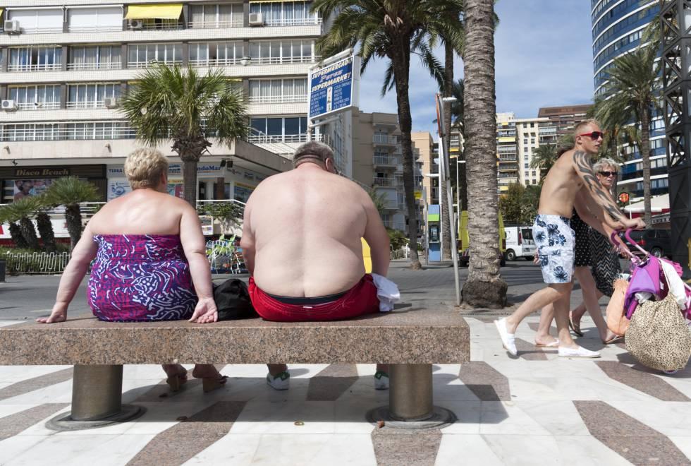 Dos personas con sobrepeso, en un banco de Benidorm.