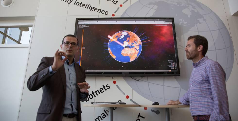 Marcos Gómez y Javier Berciano, del equipo de respuesta a incidentes del Incibe, ante una pantalla con ciberataques en tiempo real.