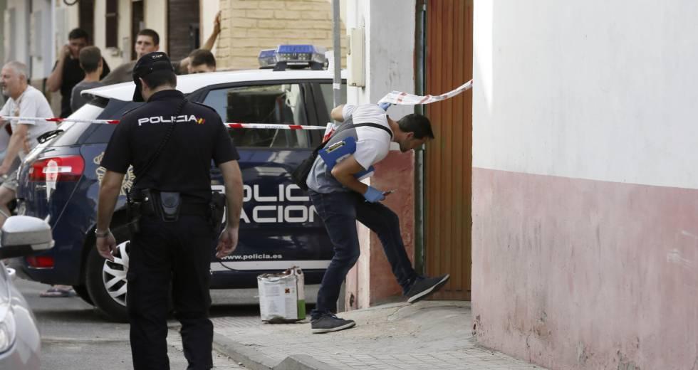 Policías junto a la vivienda donde ha sido asesinada una mujer este sábado en Sevilla.