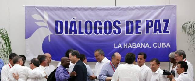Negociadores del Gobierno y las FARC se saludan tras el anuncio.