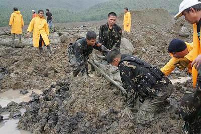 Soldados filipinos portan el cuerpo de una víctima rescatada del barro ayer en Guinsaugon.