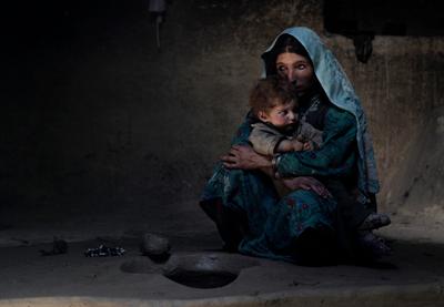 Una madre adicta al opio consuela a su hijo de un año, que llora día y noche, en una imagen de 2009. Cuando le echa humo en la cara, el pequeño se duerme. Viven en la montañosa y remota aldea de Sarab (Afganistán).