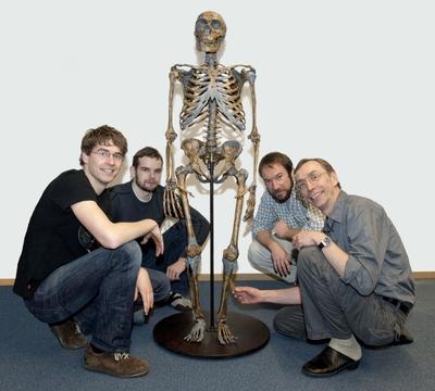 Svante Pääbo (a la derecha) y miembros del equipo que han secuenciado el genoma de neandertal junto a un esqueleto fósil de esa especie remota.