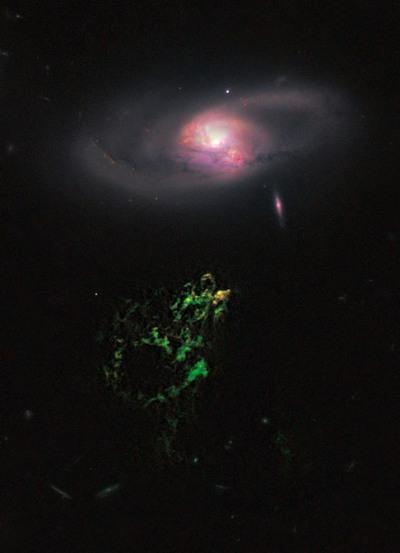 El Objeto de Hanny parece flotar debajo de una galaxia espiral, en esta imagen tomada por el telescopio  Hubble , en la que se observa en el extremo superior de la nube verde la región de formación de estrellas.