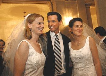 El alcalde de San Francisco, Gavin Newsom, posa junto a una pareja de lesbianas en una recepción en el Ayuntamiento.