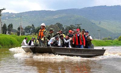 El presidente de Colombia, Juan Manuel Santos (derecha), navega por las aguas desbordadas del río Bogotá en la zona rural de Chía (Colombia). Este país pedirá en la cumbre de Durban