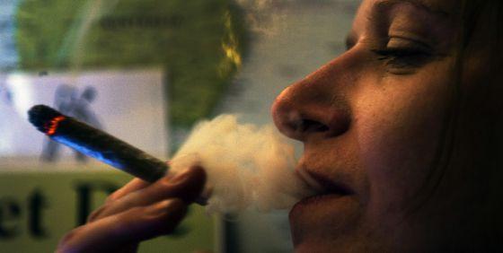 Una mujer fuma un cigarro de cannabis en un 'coffeeshop' de Ámsterdam.