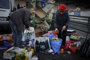 Dos mujeres recogen comida tirada en Mercamadrid.