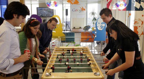 Trabajadores de Google España se relajan jugando al futbolín en la sede de la empresa durante su jornada laboral.