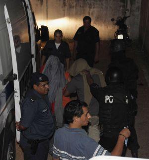La policía conduce a los enfermeros acusados de homicidios.