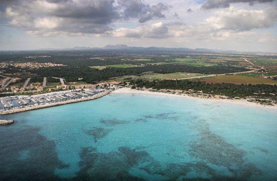 La playa de Es Trenc, en Mallorca. El macrohotel está proyectado en la zona boscosa tras el puerto deportivo.