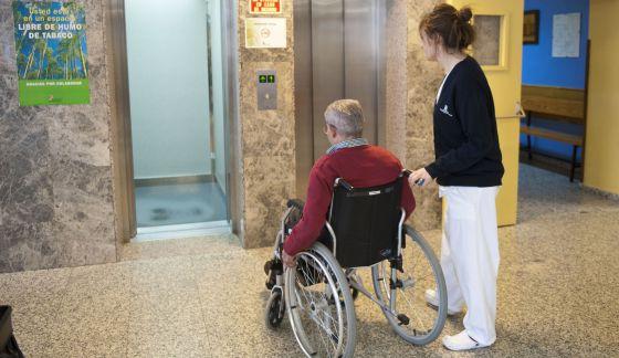 Una enfermera traslada a un paciente en silla de ruedas.