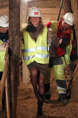 Esperanza Aguirre se quita la arena del calzado durante una visita a las obras del metro.