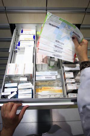 Un auxiliar de farmacia busca los medicamentos de las recetas.