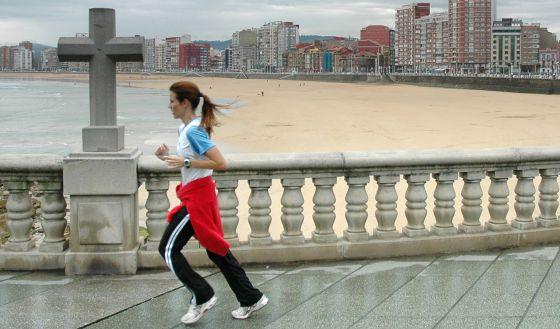 Una mujer hace ejercicio en el paseo marítimo de Gijón.
