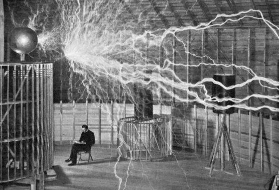 Nikola Tesla toma notas durante uno de sus experimentos.