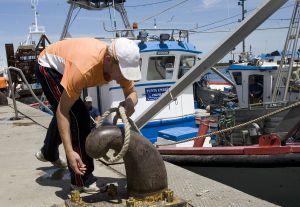Un pescador amarra su barco en un puerto de Andalucía