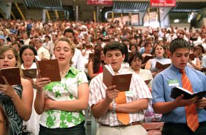 Testigos de Jehová realizan sus cánticos y rezos durante la celebración de la asamblea anual en el Palau Sant Jordi de Barcelona.