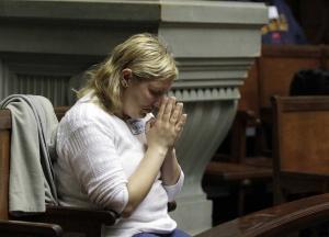 Una mujer reza mientras asiste al debate en el Senado de Uruguay.