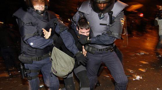 Dos agentes antidisturbios inmovilizan a un joven el 25-S en Madrid.