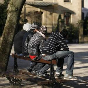 Un grupo de jóvenes, sentados en un banco.