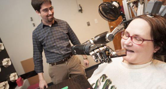 Jan Scheuemann, tetrapléjica debido a una enfermedad neurodegenerativa, se ayuda de un brazo robótico para comer chocolate.