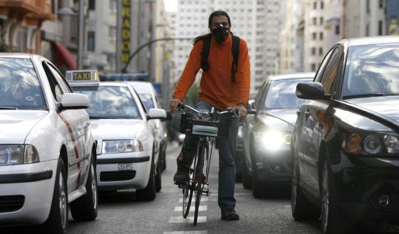 Un ciclista, con máscara para protegerse en la Gran Vía de Madrid