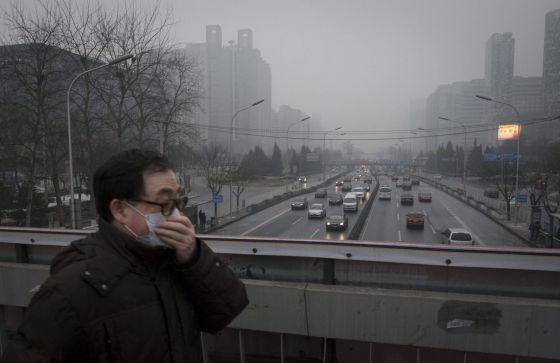 Un hombre usa mascarilla para protegerse de la contaminación en Pekín