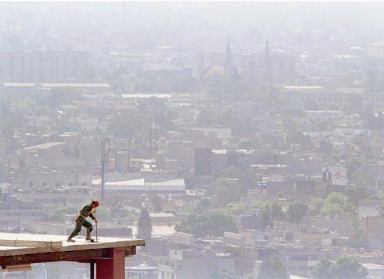 Un trabajador de la construcción en la parte superior de un edificio. Al fondo la nube contaminante