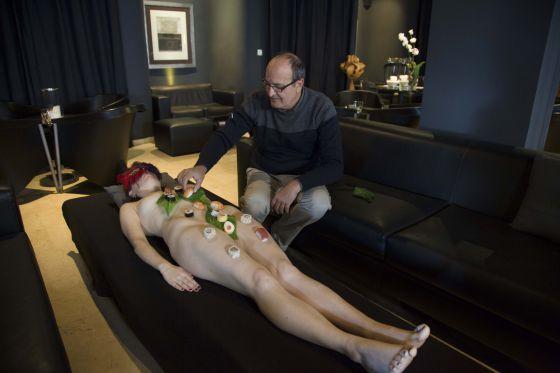 Miguel Ángel López, del Sushi Club Spain, coloca los tradicionales alimentos japoneses sobre el cuerpo de una modelo.