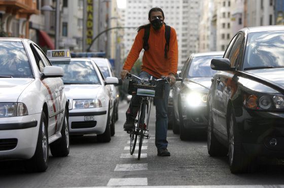 Un ciclista, con máscara para protegerse de la contaminación que producen los coches, circula por Madrid.  Samuel Sánchez
