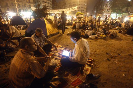 Un manifestante lee en su tableta en la plaza Tahrir de El Cairo (Egipto).