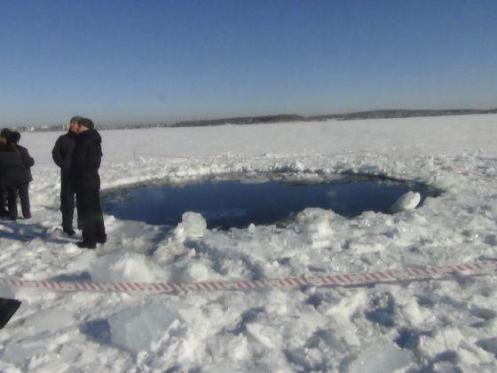 Unos hombres pasean al lado de un agujero de ocho metros en el lugar donde un meteorito impactó, en el lago congelado Chebarkul, Rusia