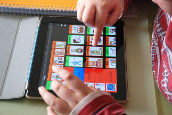 Un niño lee un cuento hecho con pictogramas.