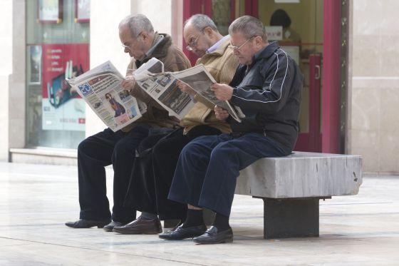 Un grupo de ancianos lee el periódico
