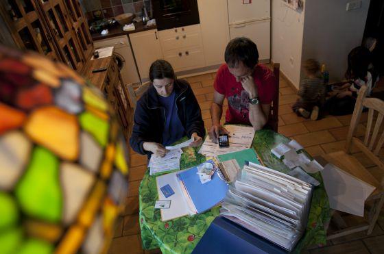 Una pareja revisa sus facturas de agua, luz y electricidad.