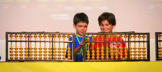 Dos niños aprenden cálculo con el ábaco japonés.