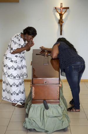 La madre de Samba Martine, de blanco, llora junto a su féretro.