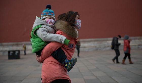 Una mujer y un bebé con máscaras a los pies de la Ciudad Prohibida de Pekín.
