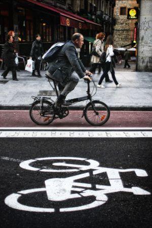 Un hombre circula con bicicleta plegable por un carril bici en el centro de Madrid.