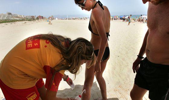 Una joven socorrista atiende a un bañista en Elche.
