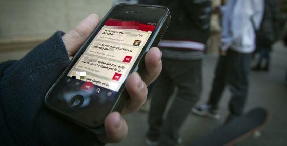 Un estudiante sostiene su teléfono móvil en la puerta de su colegio.