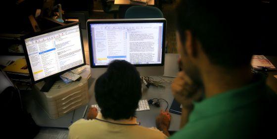Empleados de una empresa consultan su correo electrónico.