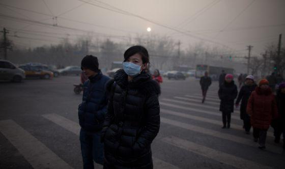 Una mujer camina por Pekín con mascarilla durante la crisis de contaminación de enero pasado.
