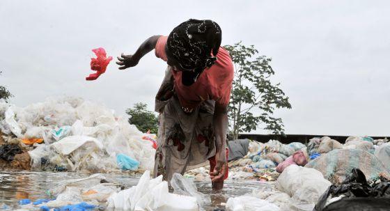 Una mujer recoge bolsas para reciclarlas en Yopougon, en Costa de Marfil.
